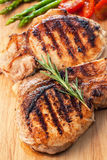 Grilled pork chop with rosemary leaf on wooden board Royalty Free Stock Image