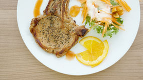 Grilled pork chop steak. Colorful salad and orange sauce Royalty Free Stock Image