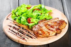 Grilled pork chop steak with fresh vegetable salad, tomatoes and sauce on wooden cutting board. Hot Meat Dishes. Top view, flat lay royalty free stock images