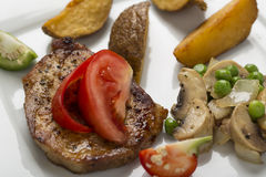 Grilled pork chop with steak fries and mixed vegetable ragout Royalty Free Stock Images