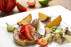 Grilled pork chop with steak fries and mixed vegetable ragout Stock Photography