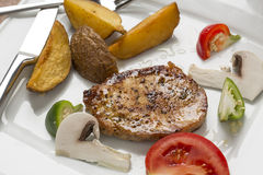 Grilled pork chop with steak fries and mixed vegetable ragout Stock Photos