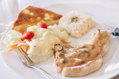 Grilled Pork chop steak with mushroom sauce. On white plate and table Royalty Free Stock Photography