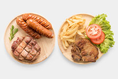 Grilled pork chop steak, sausage with french fries isolated on w Stock Image