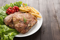 Grilled pork chop steak and vegetables with french fries on wood Stock Photography