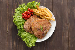 Grilled pork chop steak and vegetables with french fries on wood Royalty Free Stock Photo