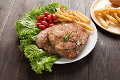 Grilled pork chop steak and vegetables with french fries on wood Stock Photo