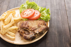 Grilled pork chop steak and vegetables with french fries on wood Stock Photos