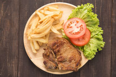 Grilled pork chop steak and vegetables with french fries on wood Stock Images