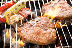 Grilled pork chop and vegetables on the flaming grill Stock Images