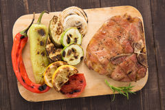 Grilled pork chop and vegetables on wooden background Royalty Free Stock Images