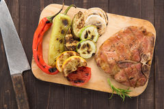 Grilled pork chop and vegetables on wooden background Royalty Free Stock Photography