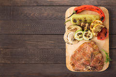 Grilled pork chop and vegetables on the wooden background. Copys Royalty Free Stock Photos