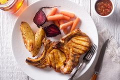 Grilled Pork Chops. Delicious barbecue grilled pork chops with roasted potato, roasted beets, carrots and relish royalty free stock image