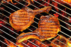Grilled pork chops. On the flaming grill royalty free stock photos