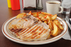 Grilled pork chops with home fries Royalty Free Stock Images