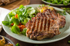 Grilled pork chops. With with salad and potato salad stock photo