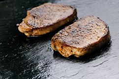 Grilled pork chops, steaks on a black slate. Fresh meat with foam. Dark background. Grilled and barbecue concept. Royalty Free Stock Image