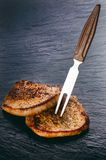 Grilled pork chops, steaks on a black slate. Fresh meat with foam. Dark background. Grilled and barbecue concept. Royalty Free Stock Photography
