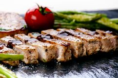 Grilled pork chops, steaks with vegetables, tomatoes, beans and sauce on a black slate. Fresh meat with foam. Dark background. Gri Royalty Free Stock Photography