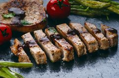 Grilled pork chops, steaks with vegetables, tomatoes, beans and sauce on a black slate. Fresh meat with foam. Dark background. Gri Stock Photography
