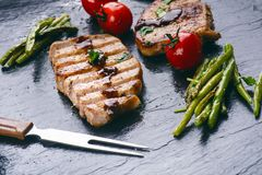 Grilled pork chops, steaks with vegetables, tomatoes, beans and sauce on a black slate. Fresh meat with foam. Dark background. Gri Royalty Free Stock Photos