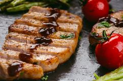 Grilled pork chops, steaks with vegetables, tomatoes, beans and sauce on a black slate. Fresh meat with foam. Dark background. Gri Stock Images