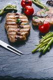 Grilled pork chops, steaks with vegetables, tomatoes, beans and sauce on a black slate. Fresh meat with foam. Dark background. Gri Royalty Free Stock Images