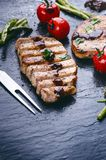 Grilled pork chops, steaks with vegetables, tomatoes, beans and sauce on a black slate. Fresh meat with foam. Dark background. Gri Royalty Free Stock Image