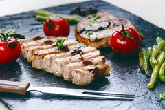 Grilled pork chops, steaks with vegetables, tomatoes, beans and sauce on a black slate. Fresh meat with foam. Dark background. Gri. Lled and barbecue concept royalty free stock photography