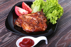 Grilled pork chops with tomato, leaves lettuce and ketchup on plate. Stock Photo