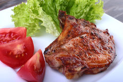 Grilled pork chops with tomato, leaves lettuce and ketchup on plate. Royalty Free Stock Photo
