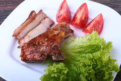 Grilled pork chops with tomato, leaves lettuce and ketchup on plate. Stock Images