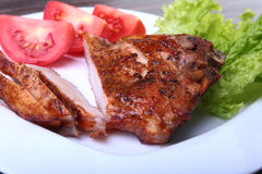 Grilled pork chops with tomato, leaves lettuce and ketchup on plate. Royalty Free Stock Images