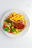 Grilled pork cutlet meat garnished with potato and salad on black table Royalty Free Stock Photo