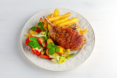 Grilled pork cutlet meat garnished with potato and salad on black table Royalty Free Stock Images