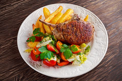Grilled pork cutlet meat garnished with potato and salad on a wooden table. Royalty Free Stock Photos