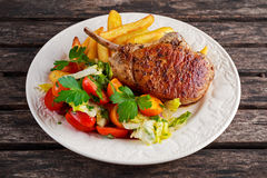 Grilled pork cutlet meat garnished with potato and salad on a wooden table. Stock Photography