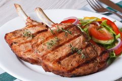 Grilled pork with fresh vegetables on a white plate. close up Royalty Free Stock Photos