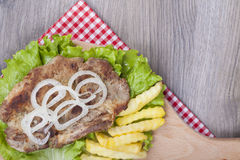 Grilled pork with fries, fresh lettuce and onions Stock Photos
