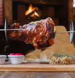 Grilled pork knuckle on spit in restaurant near fireplace Royalty Free Stock Photography