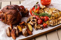 Grilled pork knuckle with grilled tomatoes, champignons, vagetable marrow, eggplant, red sweet pepper and baked potatoes stock images