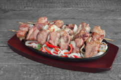 Grilled pork with lemon, salad of sweet peppers and onions, on a gray wooden background. Stock Photo