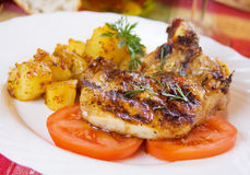Grilled pork loin chop. Served over tomato slices with baked potato Stock Photo