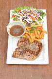 Grilled pork loin chop with French fries and salad on wood table Stock Photo