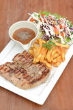 Grilled pork loin chop with French fries and salad on wood table Stock Image