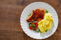 Grilled pork loin with mashed potatoes and salad in white plate on wooden table background with copy space. top view royalty free stock photo