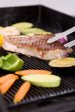 Grilled pork meat with vegetables. On barbecue Stock Photos
