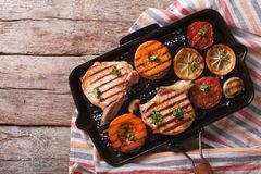 Grilled pork and pumpkin on a grill pan. Horizontal top view Stock Photo