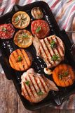 Grilled pork and pumpkin on a grill pan. Vertical top view close Royalty Free Stock Photos